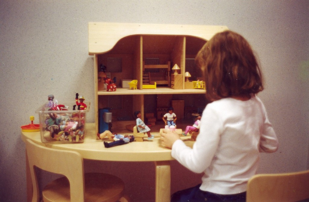 Girl playing with the doll house